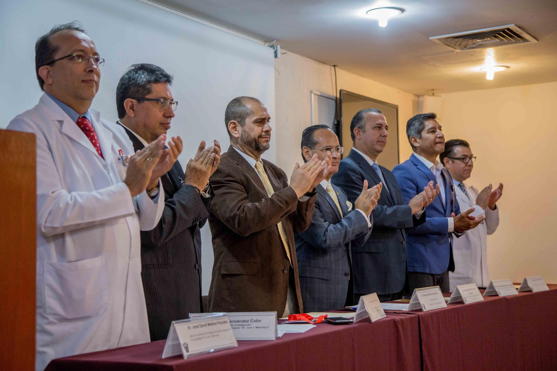 Las autoridades del presidium aplauden de pie a los beneficiados por las becas