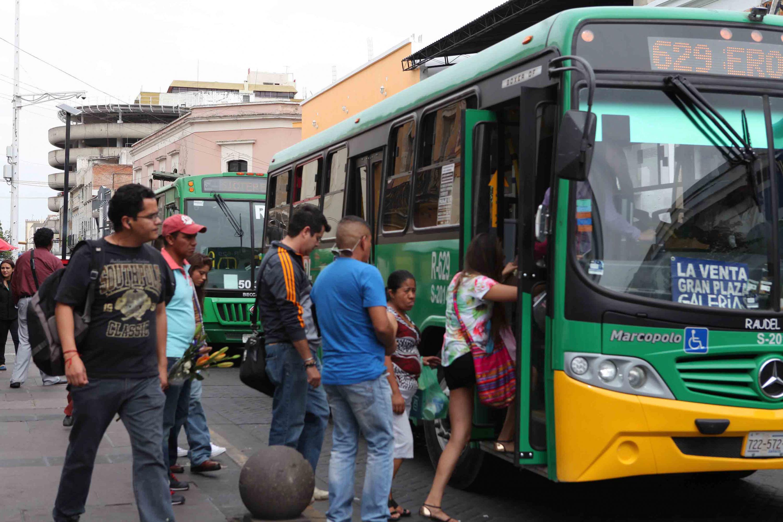Pasajeros subiendo a ruta de transporte que transita por calles del centro de la ciudad.