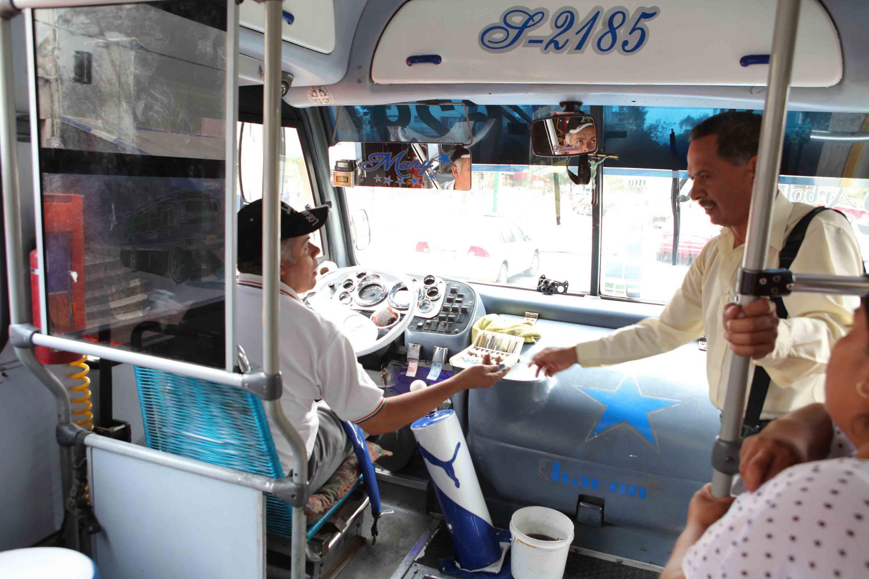 Chofer de camión, entregando boleto por su pago a pasajero.