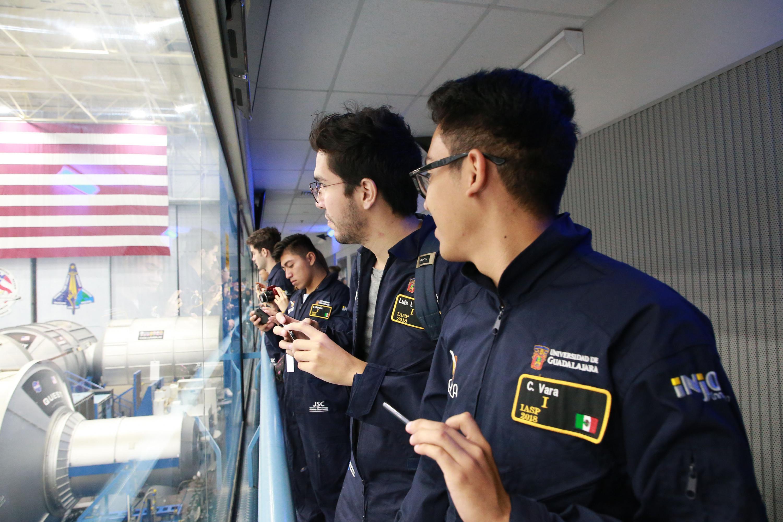 Estudiantes miran por una vitrina el hangar con vehiculos espaciales