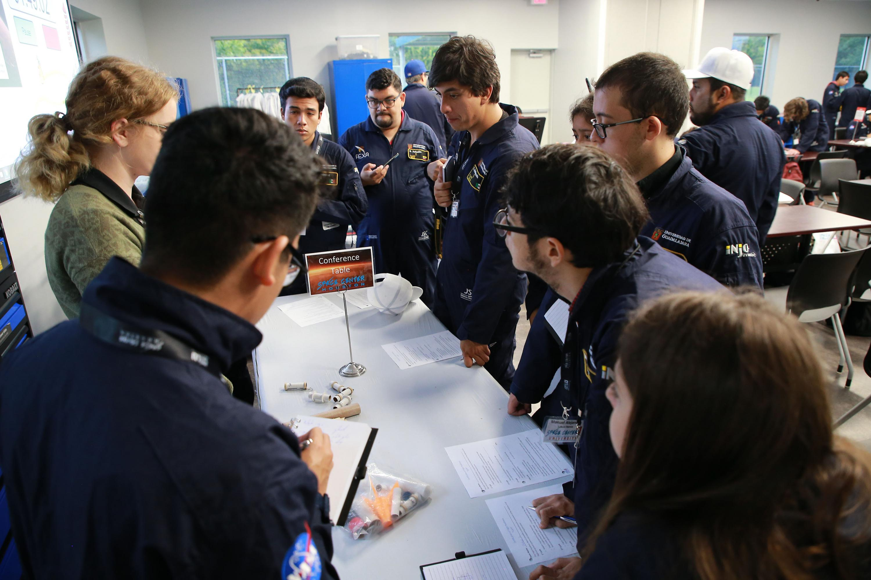 Un grupo de participántes prestan atencion a la explicacion de uno de los expertos de la NASA