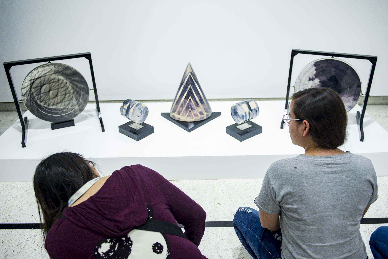 Dos jovenes observan cinco esculturas presentadas en la exhibicion del MUSA