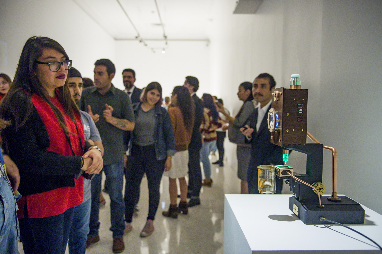 Un grupo numeroso de personas observan las obras artisiticas presentadas en el MUSA