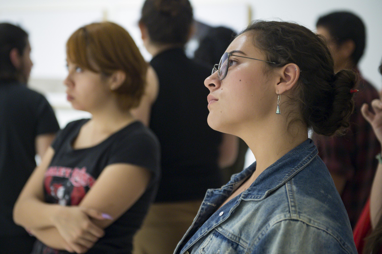 Dos mujeres jóvenes observan con atención una obra artística