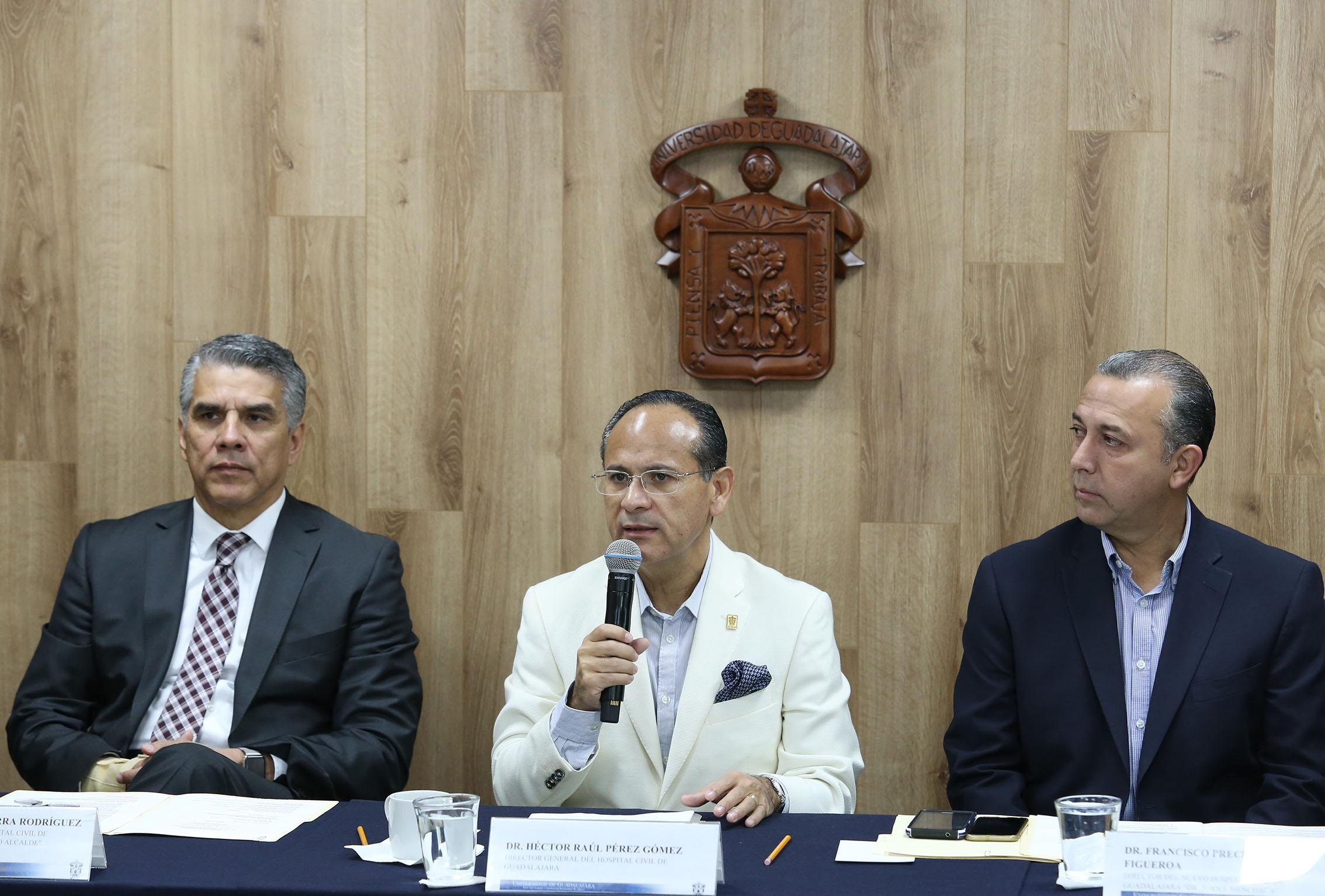 El doctor Héctor Raúl Pérez Gómez hablando al microfono  con dos medicos sentados en ambos lados de la mesa
