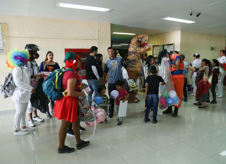 Pacientes de pediatría recibiendo juguetes por parte de diversos personajes infantiles, durante festival de entretenimiento.