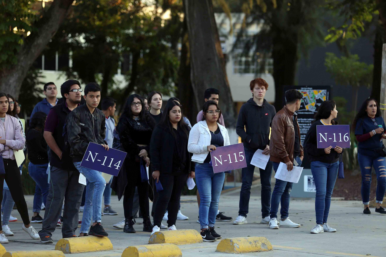 Jovenes formados en uno de los jardines de un centro universitario esperando