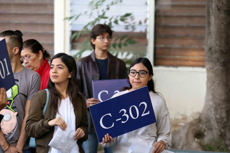 Tres jovenes aspirantes sostienen un cartel donde se lee una clave de grupo para ingresar
