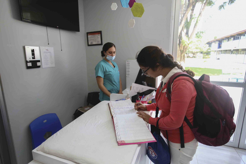 Estudiante universitaria del plantel, firmando el libro entrada y salida de la Estancia Infantil.
