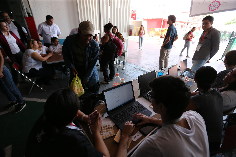 Voluntarios apoyando a la caravana de migrantes, en las instalaciones del auditorio Benito Juárez.