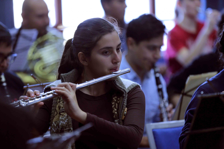 Una joven de la orquesta sinfonica tocando la flauta