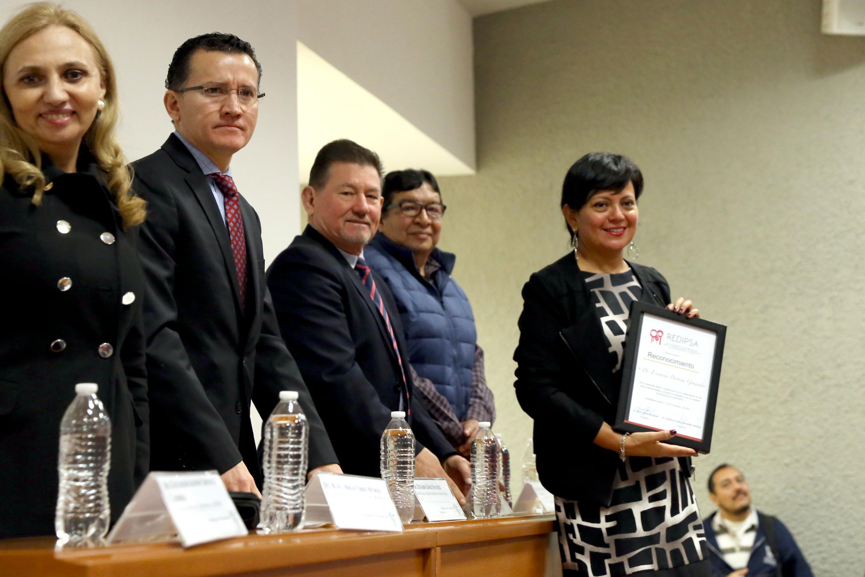 Momento en que fue entregado el reconocimiento a la COMSOC UDG por parte de REDIPSA