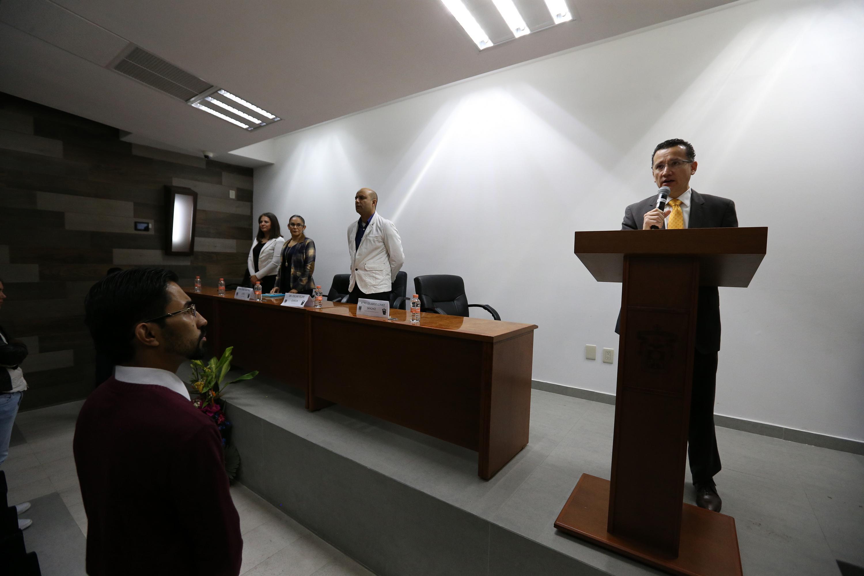 Doctor Eduardo Gómez Sánchez, coordinador de carrera, en podium del evento y con micrófono en mano, haciendo la clausura del evento.