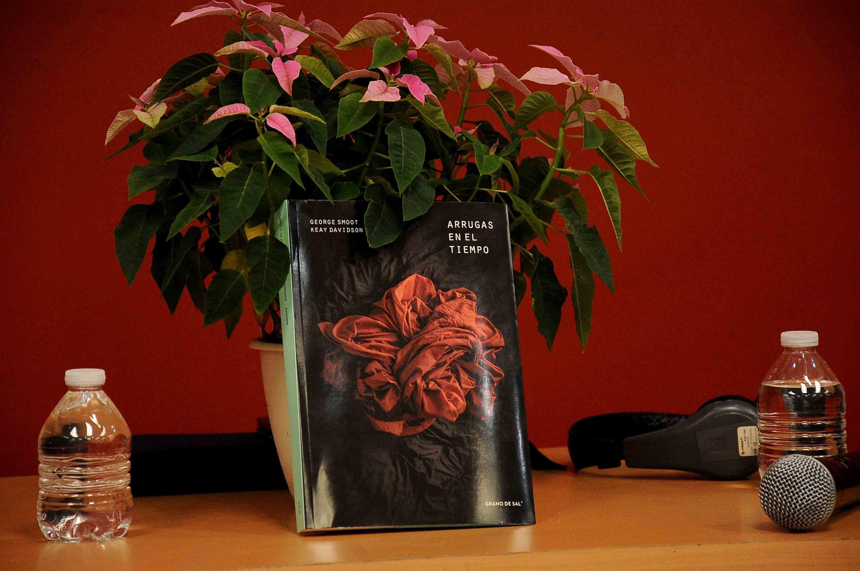 El libro del doctor George Fitzgerald Smoot titulado Arrugas en el Tiempo recargado contra una arreglo florar