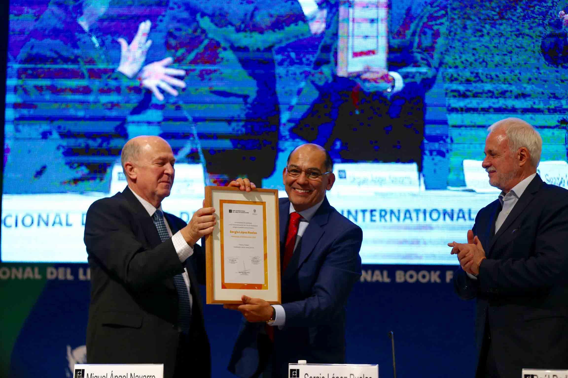 Presidente de la feria, licenciado Raúl Padilla López y el Rector general doctor Miguel Ángel Navarro Navarro haciendo entrega del reconocimiento al doctor Sergio López Ruelas