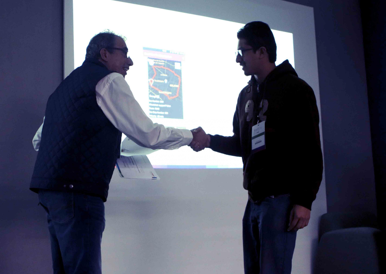 Participante y ganador de reto, recibiendo reconocimiento de participación.