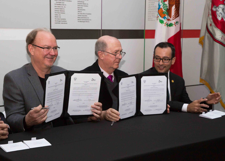 Rector General de la Universidad de Guadalajara, doctor Miguel Angel Navarro Navarro; y directivo del Instituto Tecnológico de Massachusets; mostrando el convenio firmado.