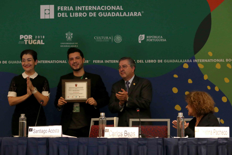 El poeta venezolano Santiago Acosta sosteniendo su reconocimiento.