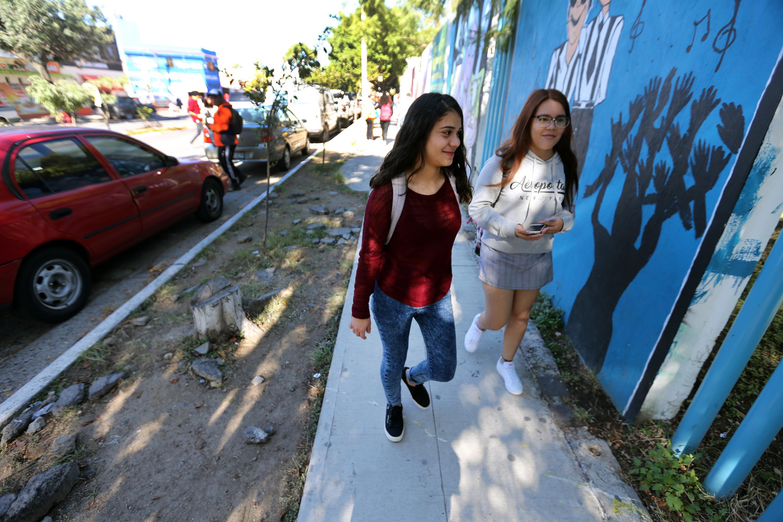 Dos jovenes estudiantes de preparatoria caminando por la calle