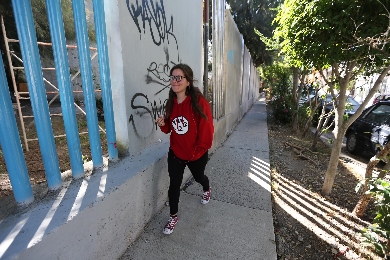 Una alumna de sudadera roja camina por la calle