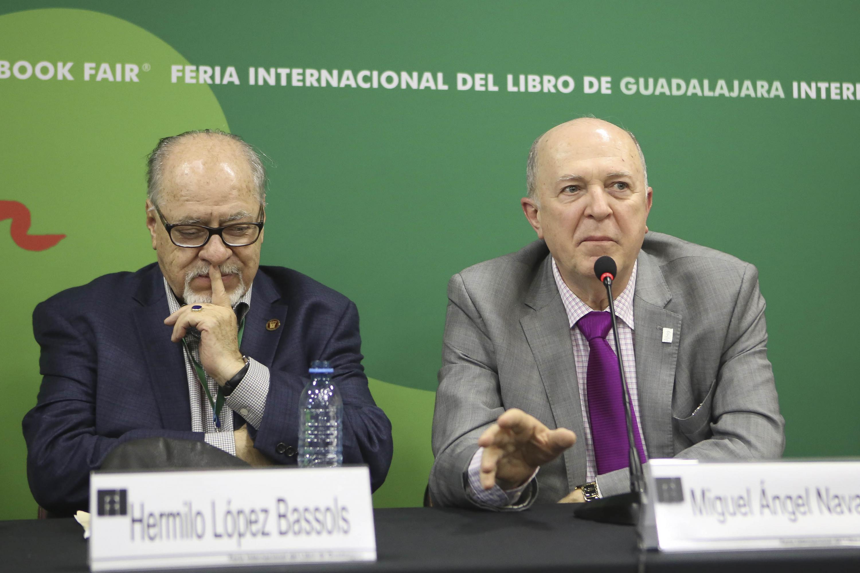 El El doctor Miguel Ángel Navarro Navarro sentado junto al autor en la mesa de presidium