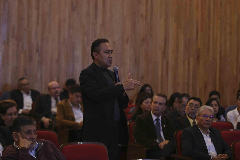Hombre del público, realizando una pregunta a los expositores, con micrófono en mano.