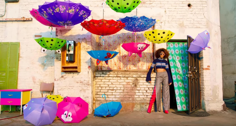 Escena del video con una cantante de reguetton rodead en un escenario con paraguas multicolores