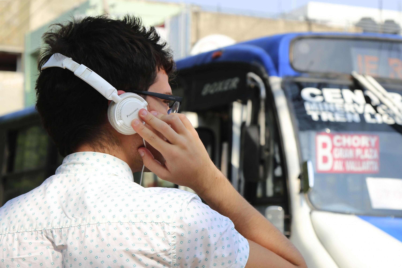 Un joven en una calle de Guadalajara escuchando musica con sus  audifonos blancos
