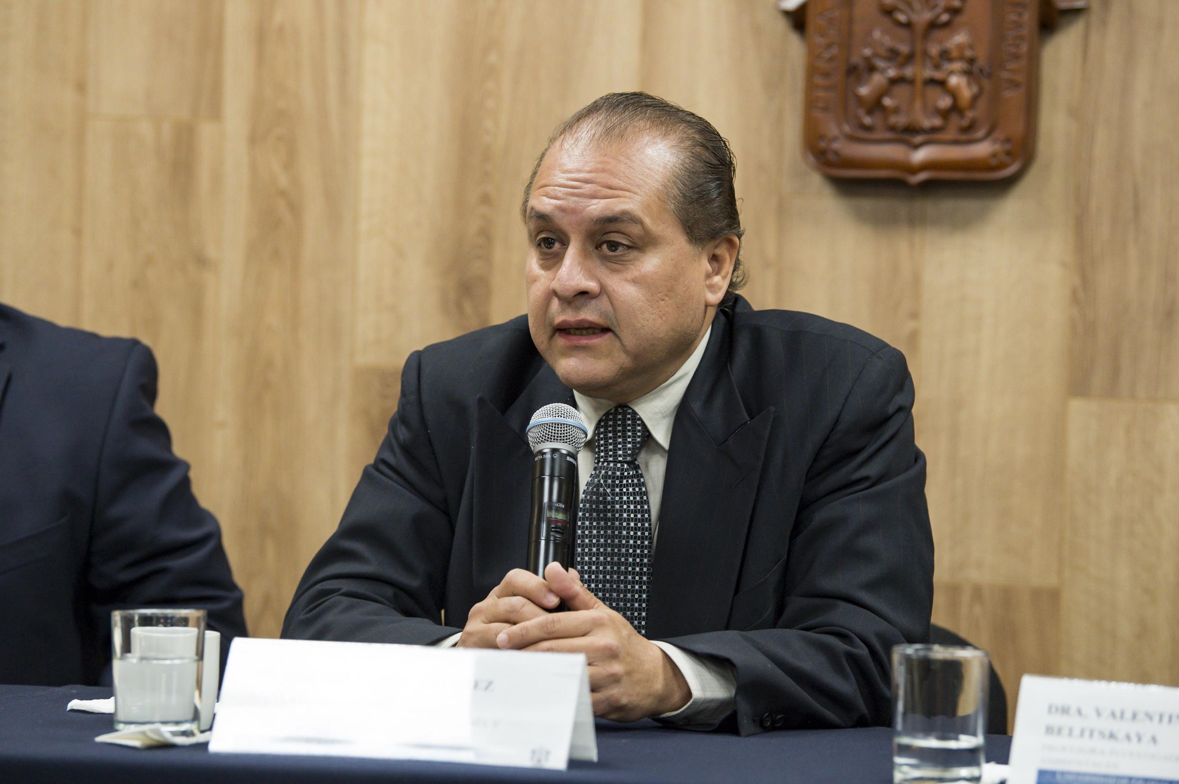 El doctor Hermes Ulises Ramírez hablando al micrófono desde su lugar en la mesa