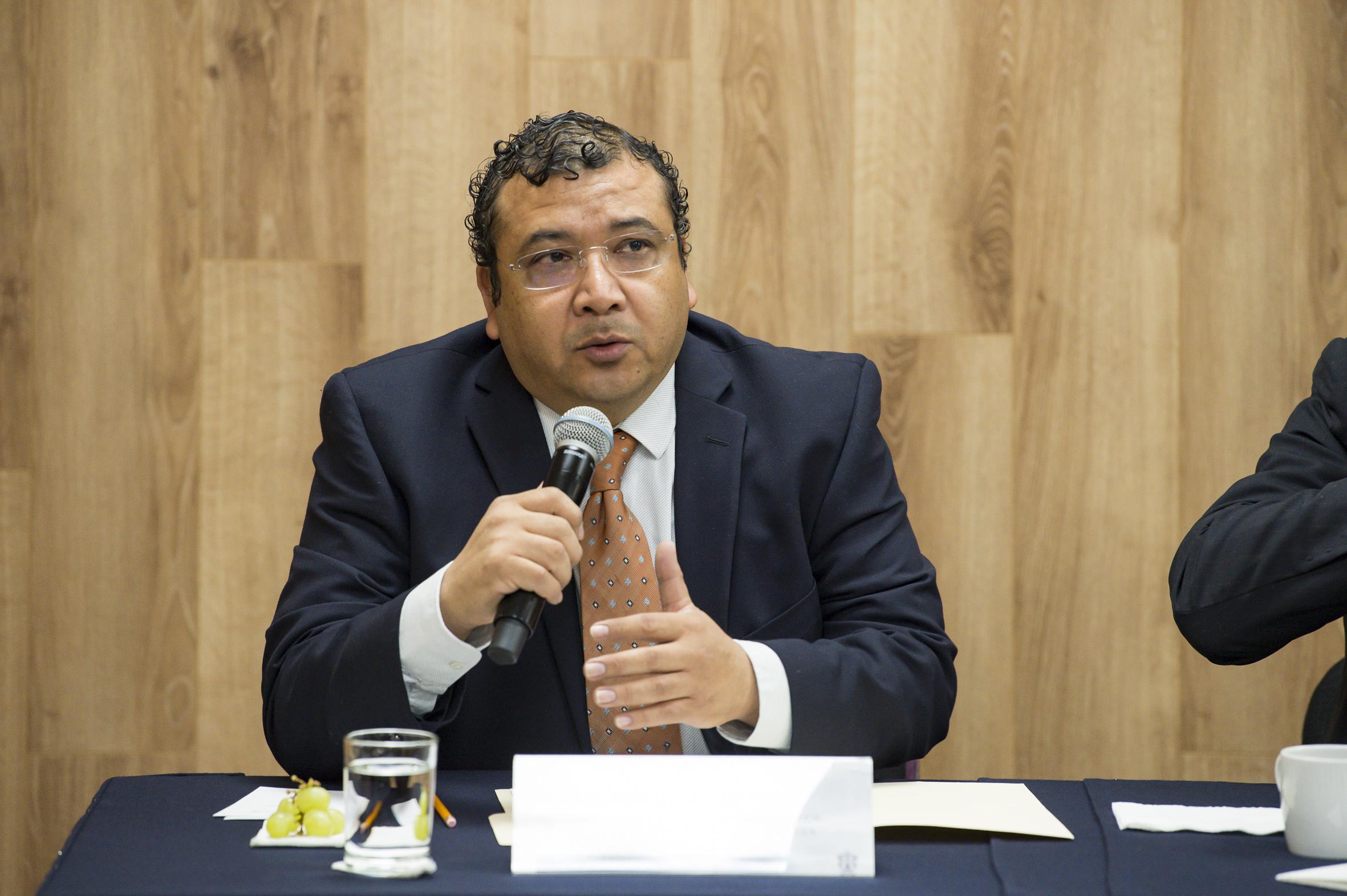 El doctor Gerardo Rojas hablando al micrófono desde su lugar en la mesa