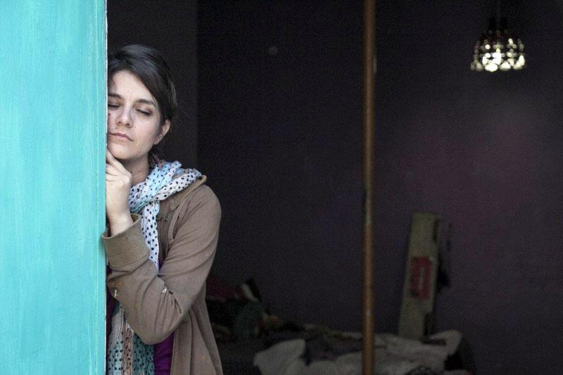 """Partes de la escena de la película """"Los años azules"""", donde una mujer jóven vestida casualmente, se encuentra soñolienta y recargada en la puerta de entrada del cuarto, teniendo la cara frente a la salida y observándose una cama destendida."""