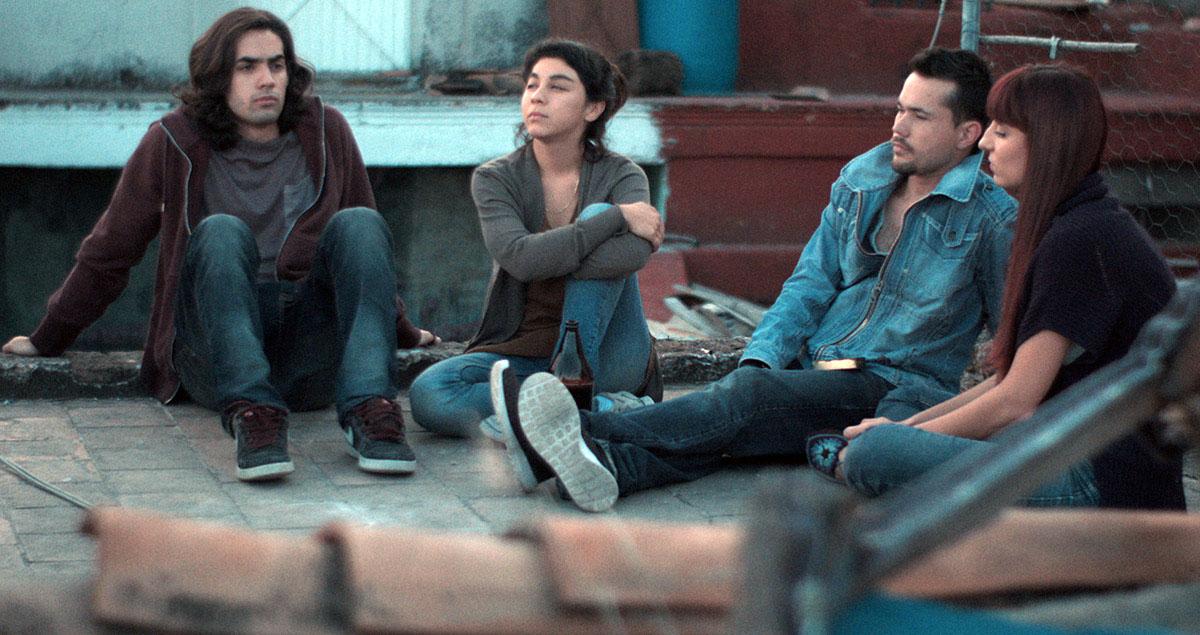 """Partes de la escena de la película """"Los años azules"""", donde un grupo de jóvenes se encuentran sentados en el suelo de la azotea de una casa antigua y de forma reflexiva; observándose en medio de ellos, una botella de caguama."""