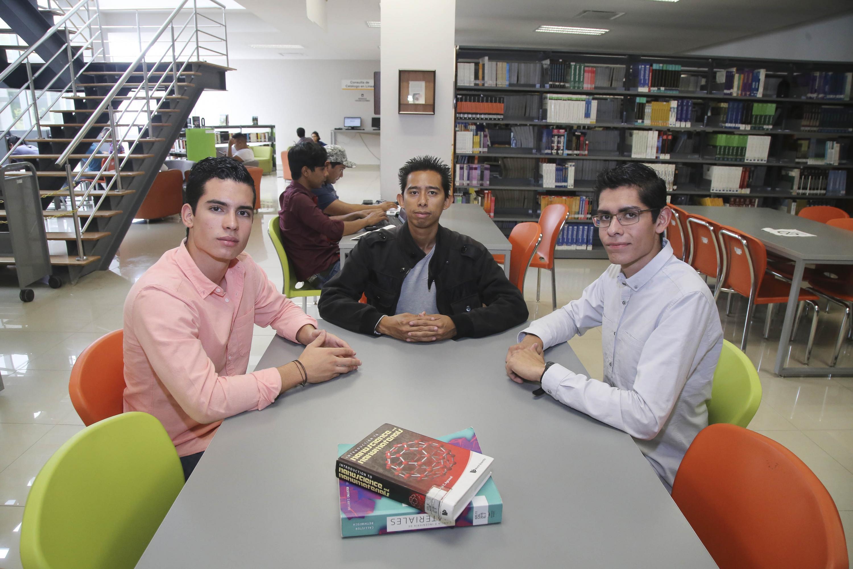 Tres jovenes sentados en una mesa de la biblioteca mirando hacia la camara