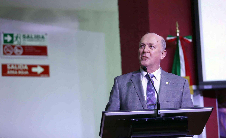 El rector general de la Ude G hablando desde el atril del auditorio del CUCS