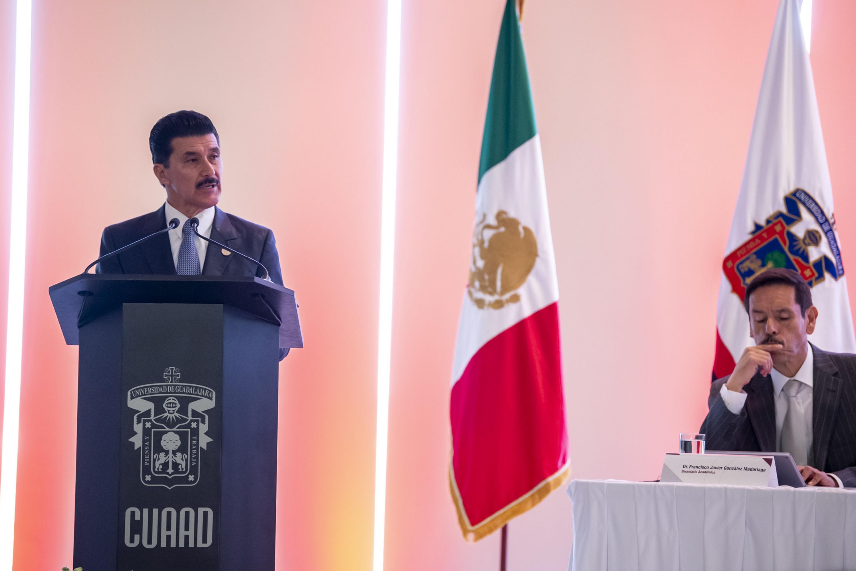 Rector de CUAAD maestro Ernesto Flores Gallo, hablando frente al micrófono durante su sexto informe de actividades