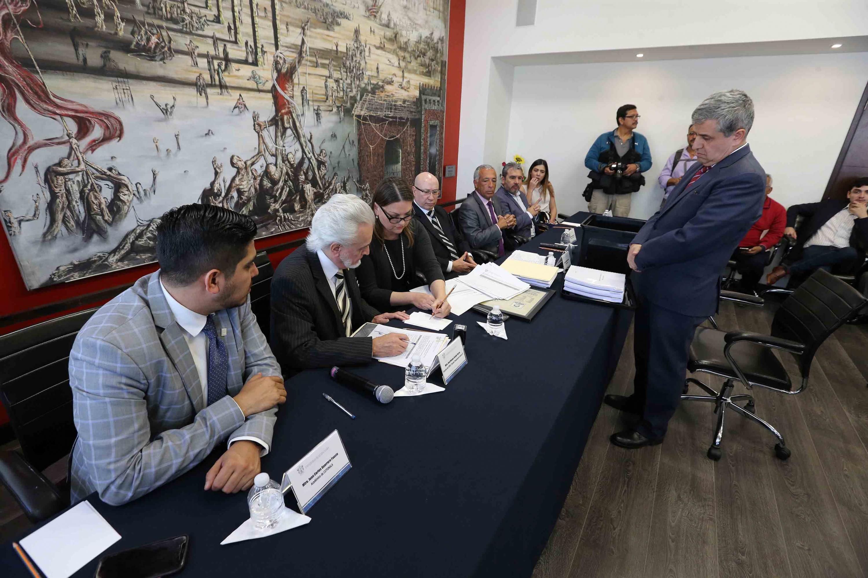 El doctor Héctor Raúl Solís observa de pie a la Comisión Electoral revisando la documentación
