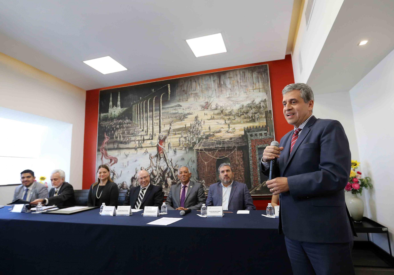 El doctor Héctor Raúl Solís hablando al micrófono frente a los miembros de la Comisión Electoral