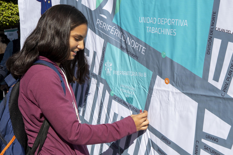 Una estudiante consulta un mapa de seguridad de la preparatoria 8