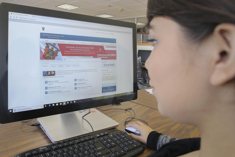 Jóven mujer, viendo el portal electrónico de la Universidad de Guadalajara.