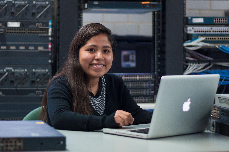 Sara Yessica Martínez Flores, estudiante de la licenciatura en Ingeniería en Telemática, del Centro Universitario de la Costa; haciendo uso de una cmputadora Mac.