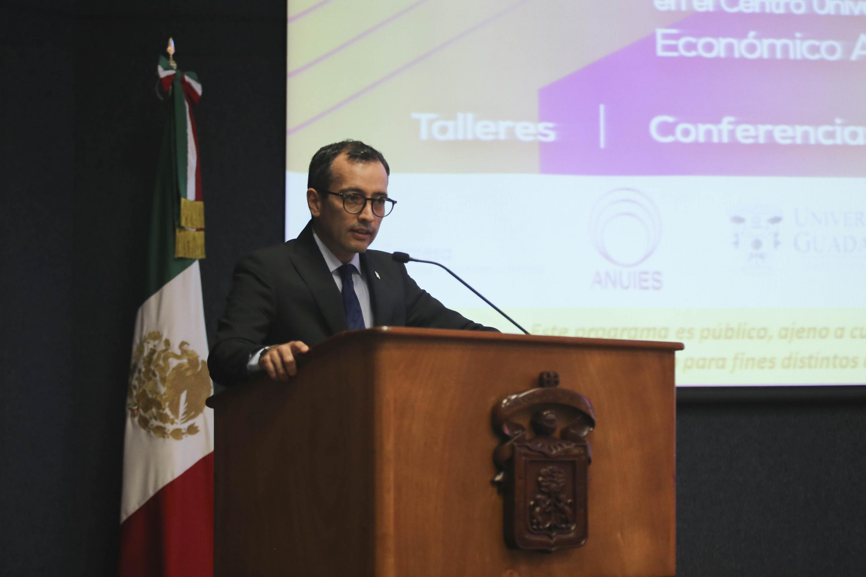 doctor Carlos Iván Moreno Arellano hablando desde el podium del auditorio de CUCEA