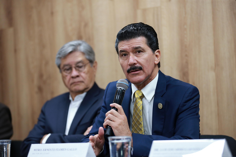 Rector del CUAAD, maestro Ernesto Flores Gallo, hablando frente al micrófono en rueda de prensa