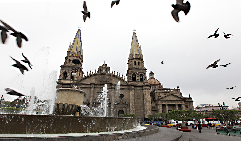 Vista panorámica de la Catedral de Guadalajara, mientra palomas descienden vuelo en la plaza alrededor de su fuente.