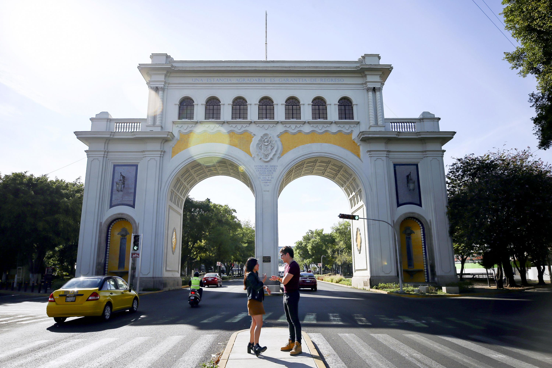 Pareja de jóvenes manteniendo una conversación sobre el camellón de los Arcos de Vallarta