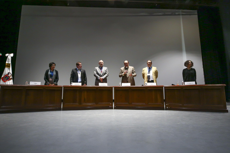 Los panelistas de pie detras del presidium