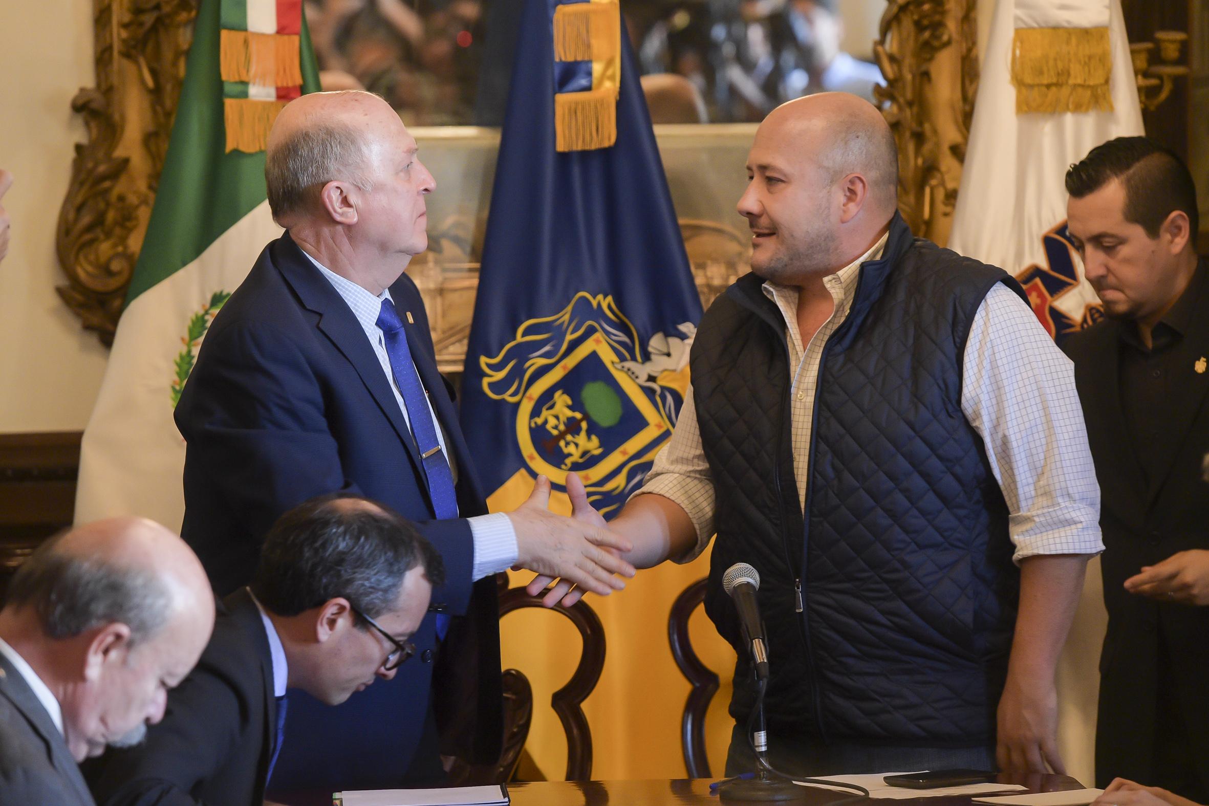Miguel Angel Navarro Navarro y Enrique Alfaro Ramírez estrechan sus manos despues de la firma del acuerdo