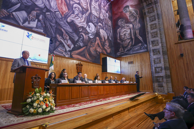 Vista general de la mesa del presidium mientras el rector General habla desde el podium