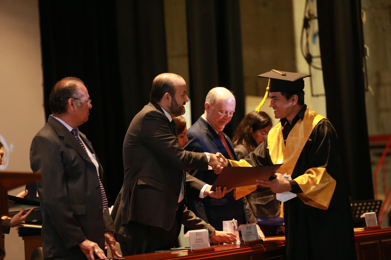 Rector del Centro Universitario de Tonalá, doctor Ricardo Villanueva Lomelí, haciendo entrega de reconocimiento a alumno egresado