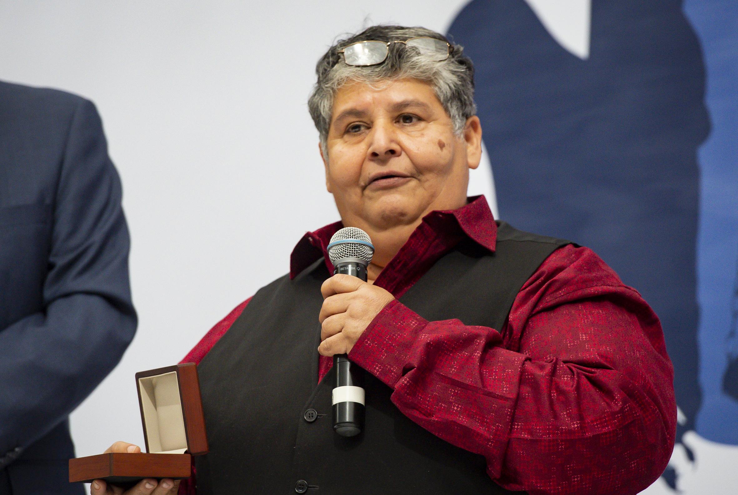Altagracia Tamayo Madueño hablando al microfono mientras sostiene en su mano el estuche con el reconocimiento
