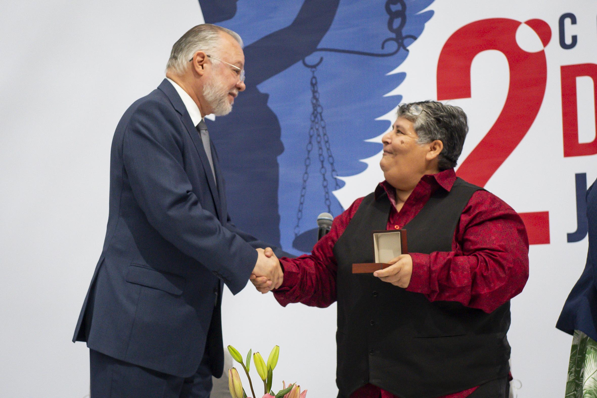 el licenciado José Trinidad Padilla López estrecha la mano de Altagracia Tamayo Madueño